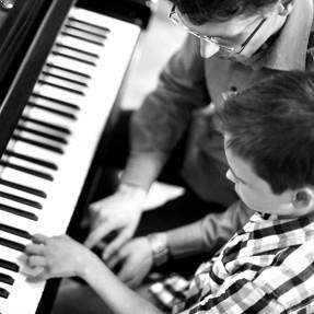 man teaching child to play the piano